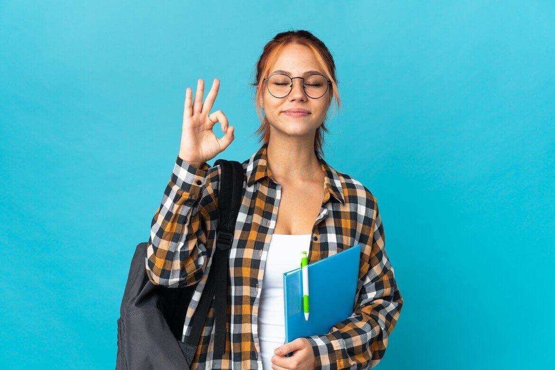 девушка-подросток, изолированные на синей стене в позе дзен