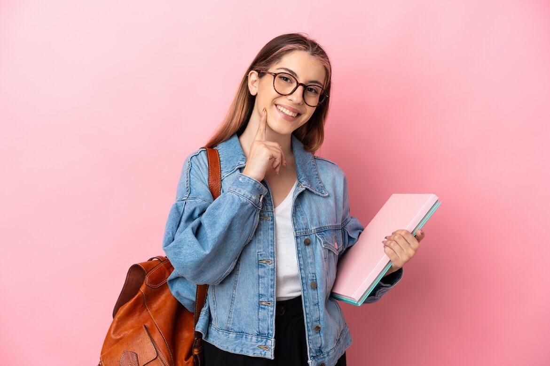 Девушка с рюкзаком и книгами улыбается