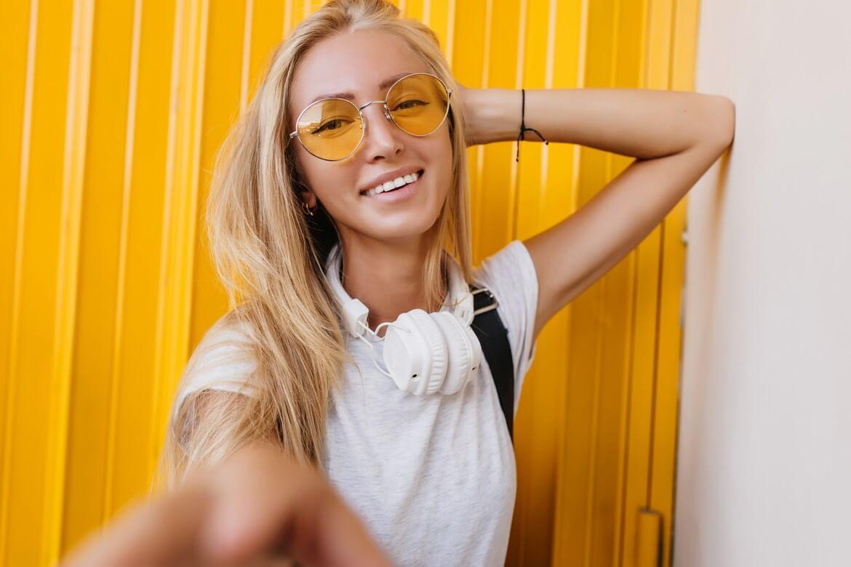 Симпатичная девушка в солнцезащитных очках, делая селфи на желтом фоне