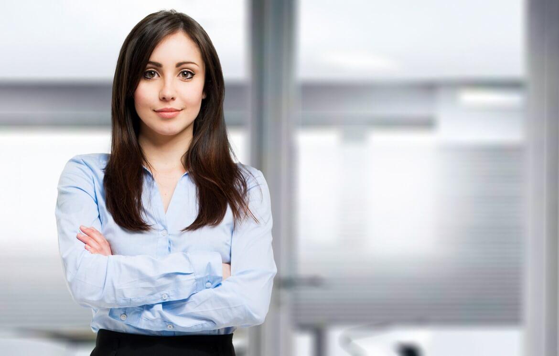 Девушка в офисной одежде стоит скрестив руки