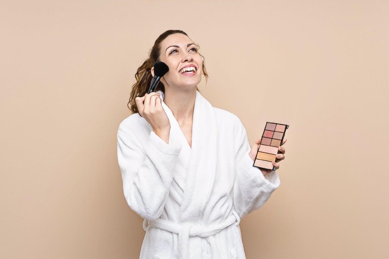 девушка наносит макияж для маскировки акне
