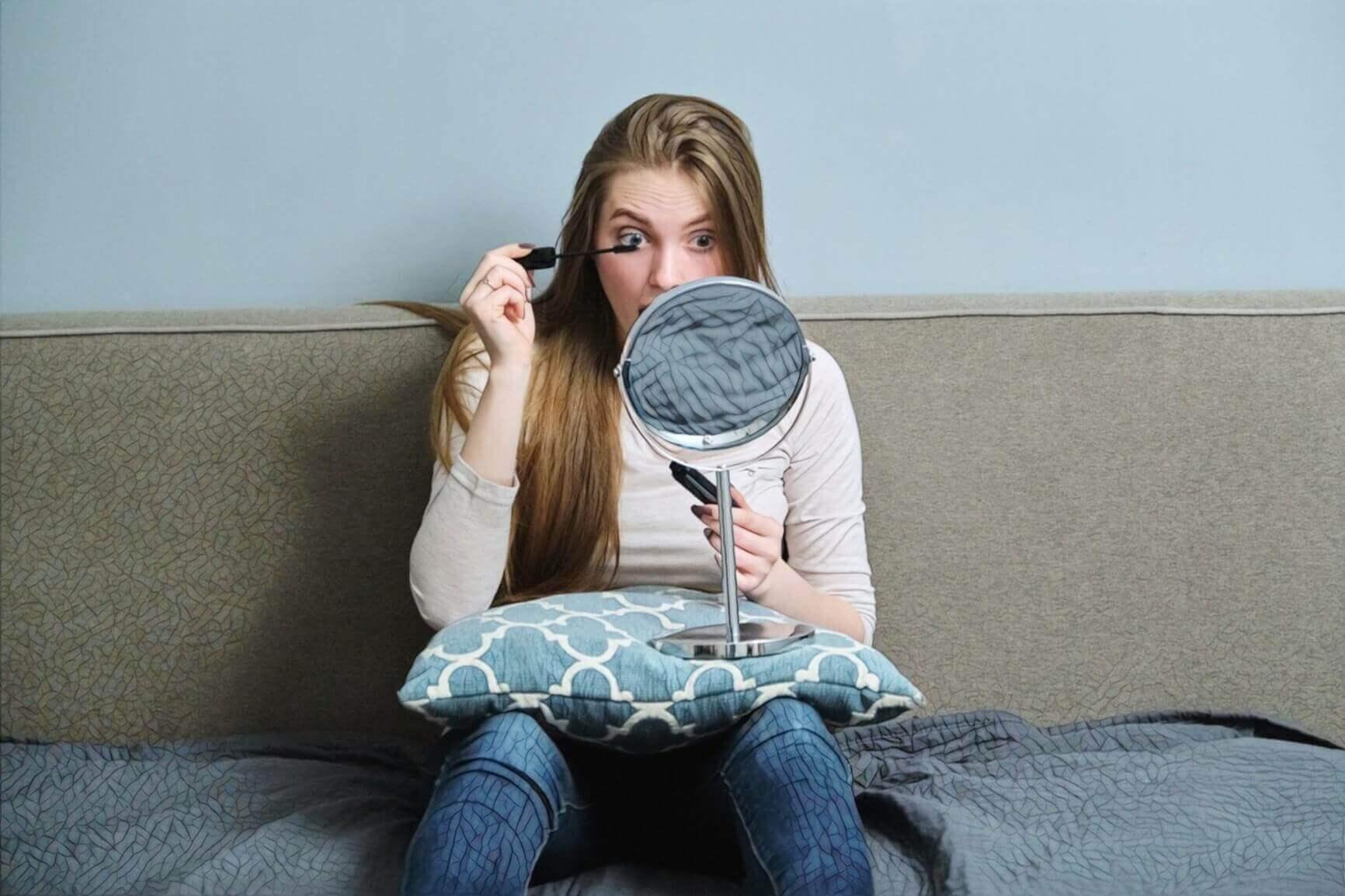 Девушка на диване делает макияж