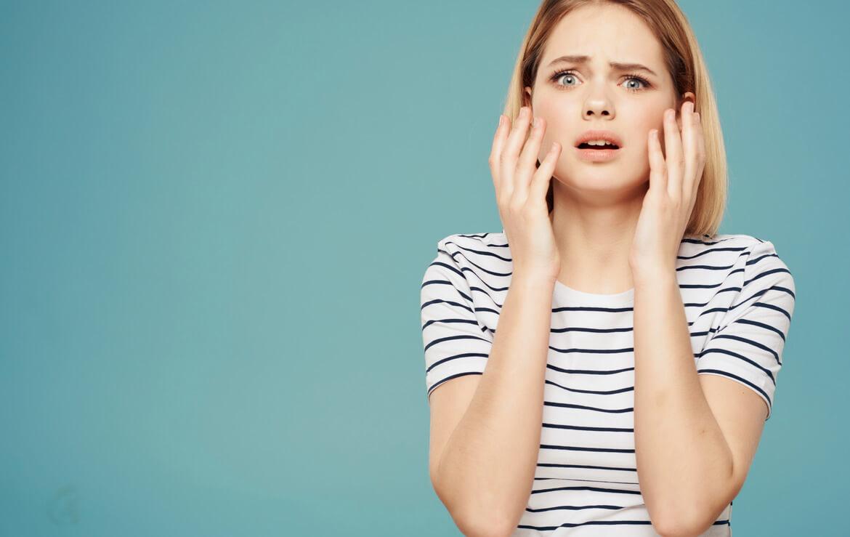 Обеспокоенная молодая женщина с руками на лице