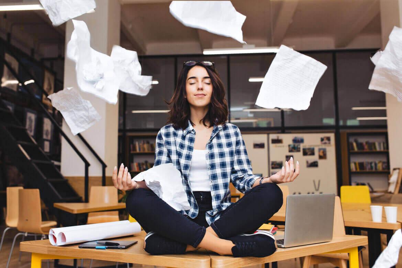 Молодая довольно радостная брюнетка женщина медитирует на рабочем столе и летающих бумагах