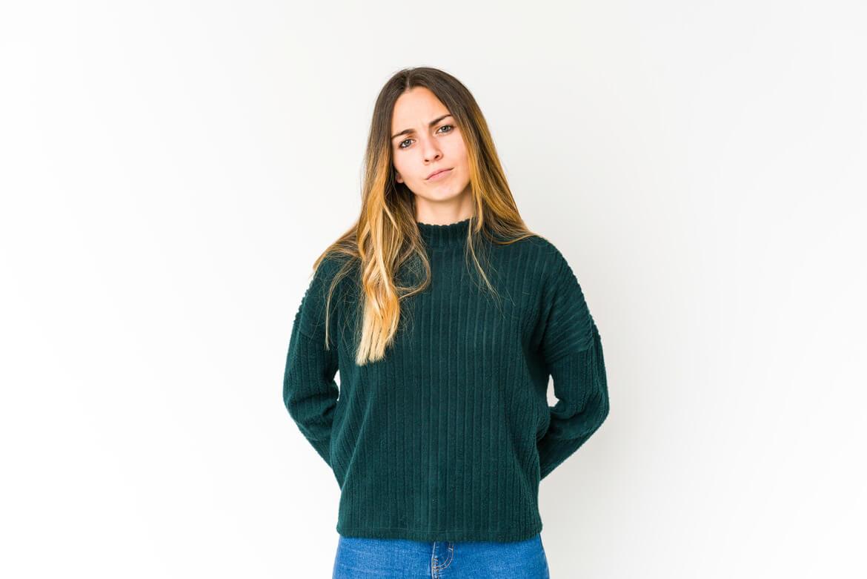 Девушка в зеленом свитере слушает