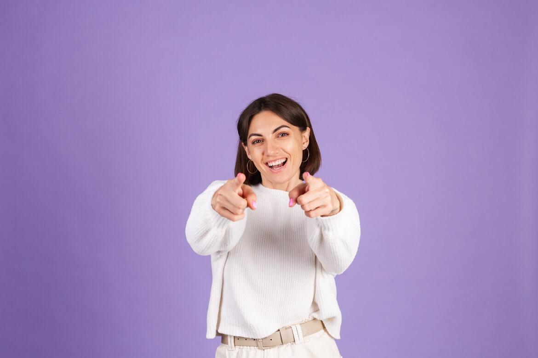 Молодая брюнетка в белом повседневном свитере изолирована на фиолетовой стене