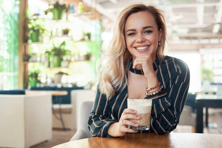 Красивая женщина держит коктейль в руках