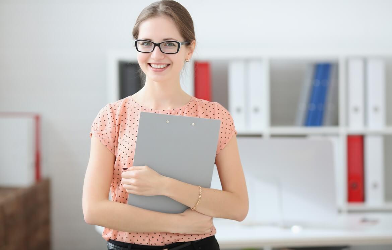 Студентка держит планшет для заметок в руках в аудитории