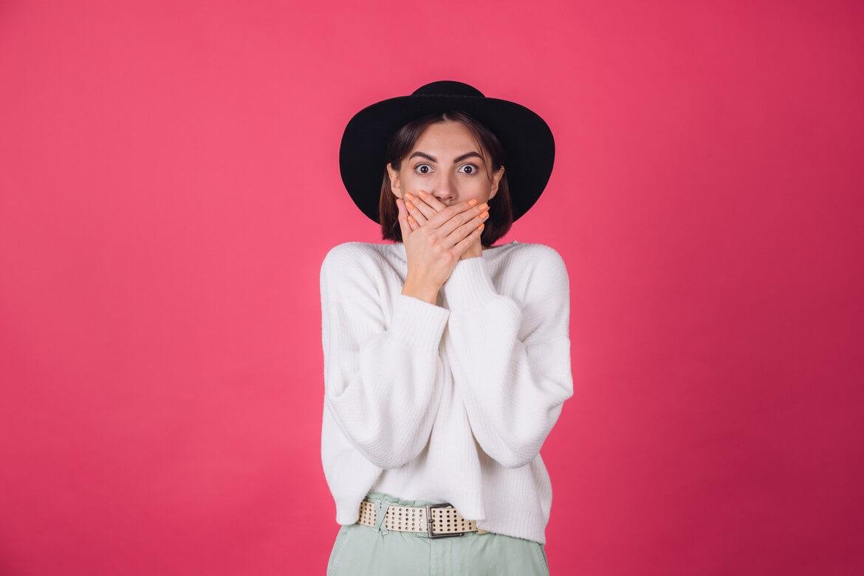 Стильная женщина в белом повседневном свитере и шляпе на красно-розовой стене