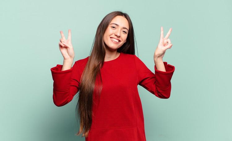 Молодая довольно непринужденная женщина улыбается и выглядит счастливой