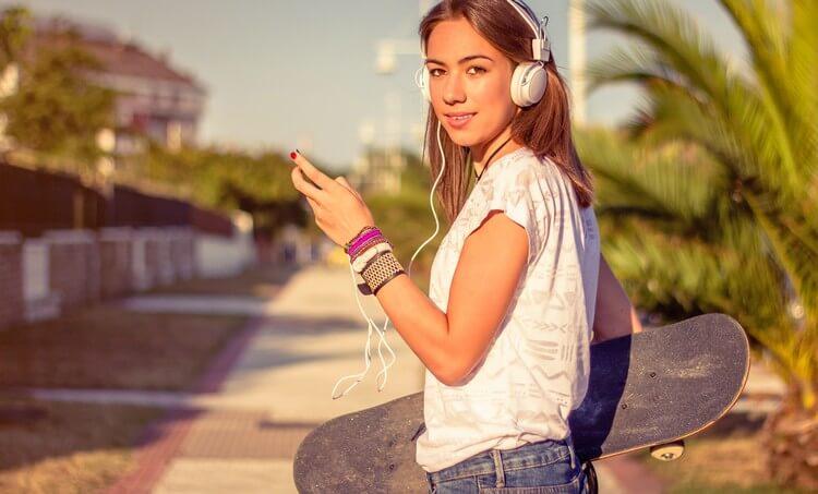 Портрет красивой молодой девушки со скейтбордом и наушниками, слушая музыку