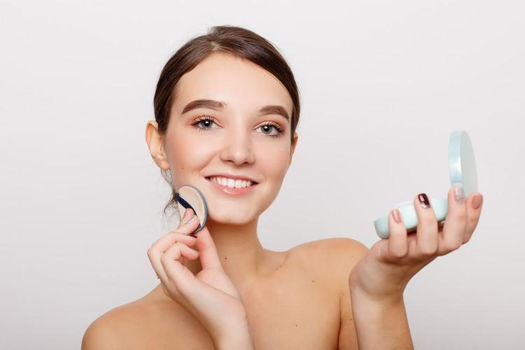 молодая женщина, наносящая румяна на лицо