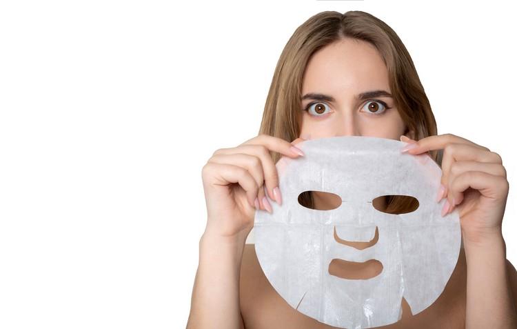 Удивленная женщина брюнет с увлажняющим с маской