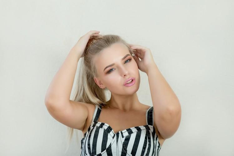 Модная блондинка с розовыми губами и красивыми голубыми глазами смотрит в камеру